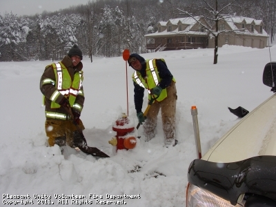 PUVFD firefighters work to clear fire hydrants covered by heavy snowfall to ensure the hydrants are accessible in an emergency.